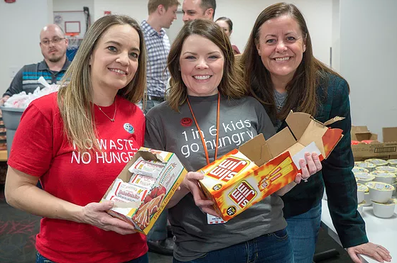 KFC and Henny Penny Employees pack 1,500 bags of food for Local Kids