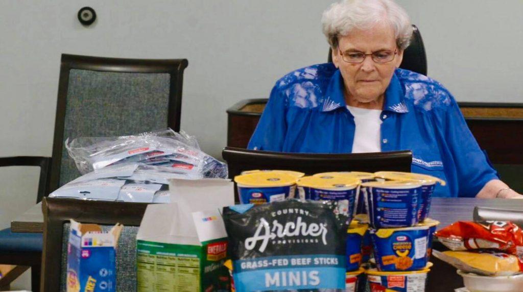 senior woman putting food in backpack